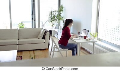 Beautiful young woman with laptop working from home. -...