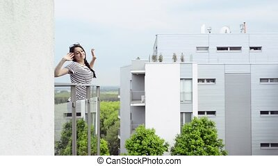 Young woman relaxing on balcony stretching her arms. -...
