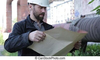 Engineer man supervisor holding blueprints plan and inspects the pipeline