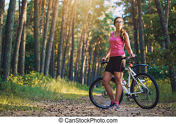 cyclist cycling mountain bike on Pine forest trail - woman...