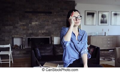 Young woman at home writing something into notebook. -...