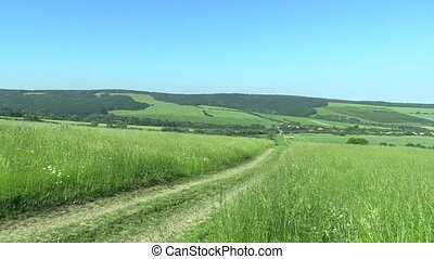 Green mountains meadows, blue sky and village, White...