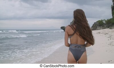 Happy young girl in the beautiful bathing suit walks along...