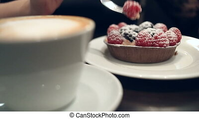 Woman eating dessert and drinking coffee in a cafe, close-up...