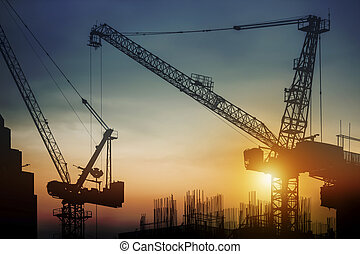 Silhouette construction site with cranes at sunset