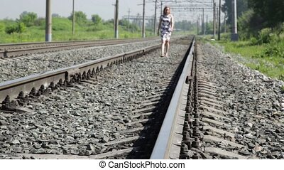 beautiful woman walking along railway tracks in a sun day.