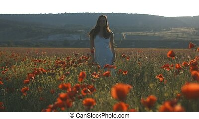 Young happy girl walking and smiling in poppy field
