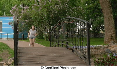 A young beautiful girl runs across the bridge of love to...