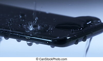 Drops of water falling on the phone screen in slow motion....