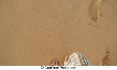 Point of view of young man stepping at the golden sand at...
