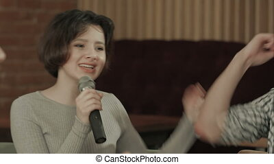 Young woman holding microphone and singing at karaoke, Close...