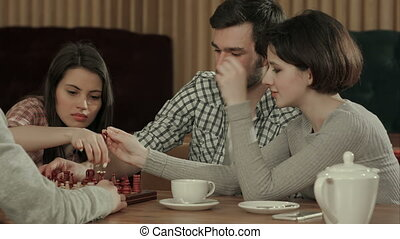 Friends playing chess laughing spending holiday....