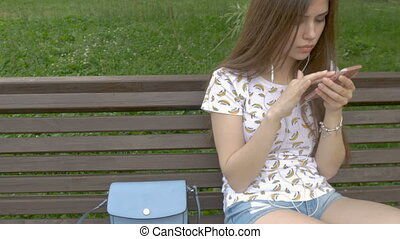 Young beautiful girl is sitting on a park bench, looking sms on a smartphone. She got bad news from my boyfriend. Sadness and sadness.