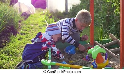 Children play with toys in the sandbox. Entertainment and outdoor games. Summer sunny day