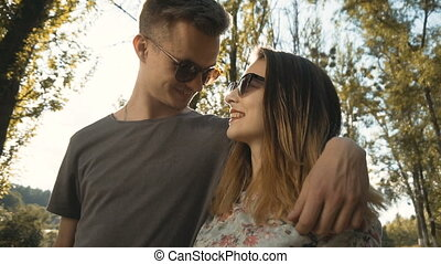 Hipsters Couple Walking - Young cute hipster couple in park,...