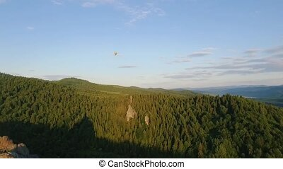 Hot Air Balloon fly through the sky in a landscape of...