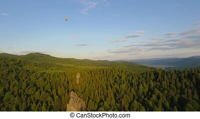 Hot Air Balloon flying across the sky in mountains landscape
