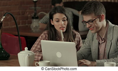 Young couple at cafe looking at laptop and smoking hookah....