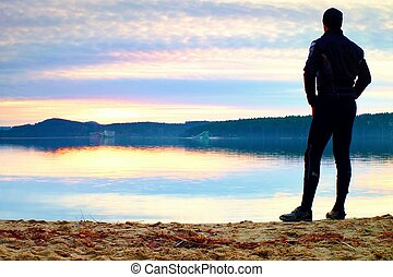 Sportsman standi on bay beach in warm sporty clothing at sunset. Autumn begins, end of season.