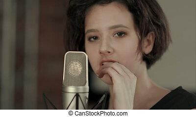 Young girl singing and looking at camera. Close up....