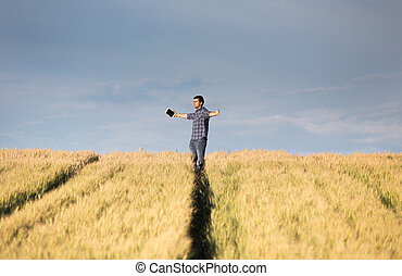 Man with outstretched arms in field