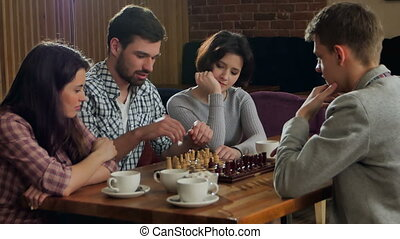 Young men and women playing chess. Professional shot in 4K...