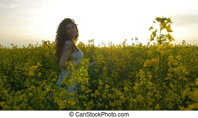 Young woman dancing and spinning in the canola flowers...