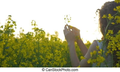 Slow motion of country girl gracefully touching a rapeseed...
