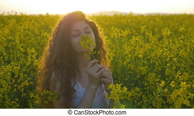 Slow motion of teenage girl in white dress spinning and smiling in rapeseed field