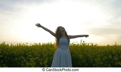 Concept of freedom with woman in nature holding hands towards the summer sky in the rapeseed field