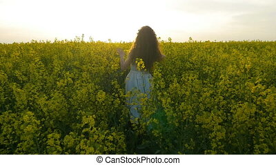 Slow motion of teenager girl walking and touching plants in rapeseed field at sunset
