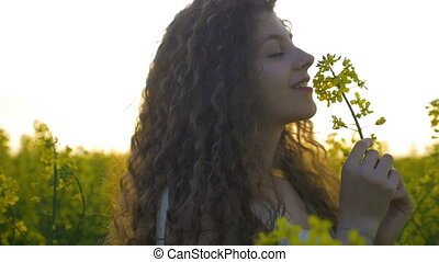 Closeup of beautiful girl smelling a canola flower and dancing in the field full of rapeseed plants