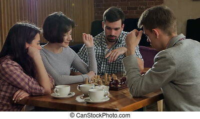 Young couple playing chess indoor with friends. Professional...