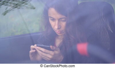 Beautiful young woman sitting in car with smartphone.