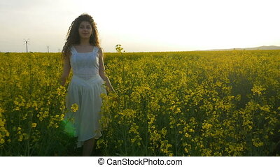 Pretty girl with white dress walking towards camera in field of rapeseed yellow flowers
