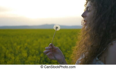 Closeup of young woman blowing dandelion seed relaxing in the countryside with golden field in the background