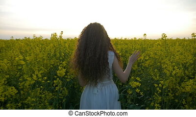 Nature loving teenager girl enjoying a slow walk on a summer day through a golden rapeseed field during her vacation at the countryside