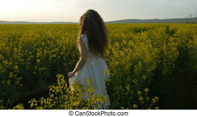 Girl in white dress walking through canola field on a sunny day