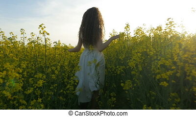 Young woman dressed in white walking and touching plants in...