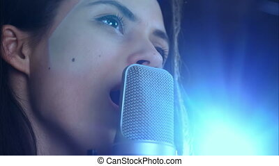 Young pretty woman singing. Close up. Professional shot in...
