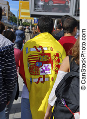 Spanish people walking the streets of Madrid with a flag of...