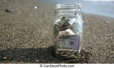 A glass jar with paper money dollars against a sea waves...