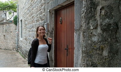 Attractive woman with interest examines a narrow street....