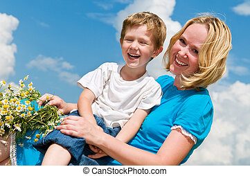 laughing mother and son - Happy mother with camomile wreath...