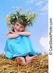 Happy smiley girl with camomile wreath outdoors over blue...