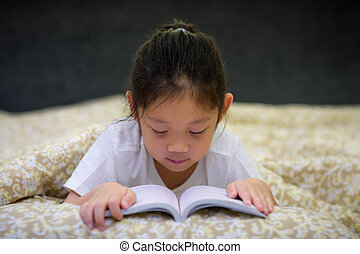 Asian Child Reading Book in Bed