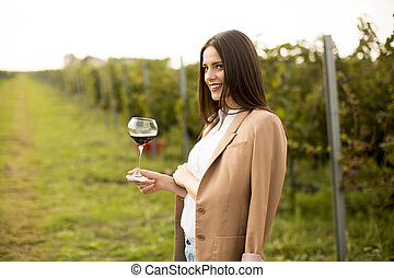 Young woman tasting wine in the vineyard