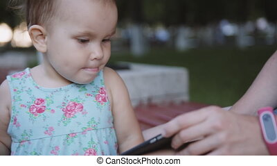 Child is watching something on the smartphone - Baby is...