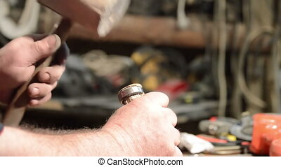 carpenter with hammer and chisel processing wood plank at...