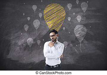 Portrait of businessman looking up at chalk balloon icons -...